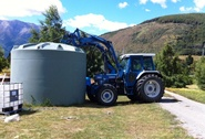 Tractor lifts 30,000 litre water tank at Muntanui biodynamic farm, South Island, New Zealand