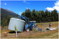 Tractor transports 30,000 litre water tank at Muntanui, South Island, New Zealand